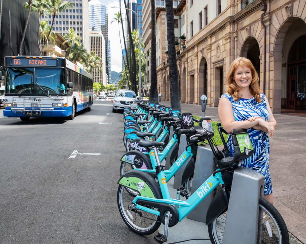 Kathleen Rooney at a bike share station, there is a #66 AIKAHI bus in the background.